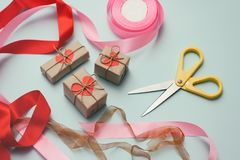 Free Gifts Wrapping Process. Decorative Paper, Silk Ribbons, Gift Boxes, Scissors. Light Blue Background. Stock Images - 153890094