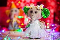 Giftstuk speelgoed olifant die zich op achtergrond van Kerstmislichten en dozen bevinden Royalty-vrije Stock Foto's