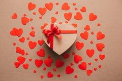Giftvakje in gerecycleerd document met rode lintboog wordt verpakt op achtergrond van rode harten dat Royalty-vrije Stock Foto