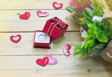 Giftvakje met harten en bloemen op houten lijst, de dagachtergrond van Valentine ` s Royalty-vrije Stock Foto
