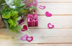 Giftvakje met harten en bloemen op houten lijst, de dagachtergrond van Valentine ` s Stock Foto's