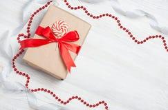 Giftvakje met rode boog op houten lijst Kerstmisachtergrond met feestelijke decoratie Plaats voor uw tekst Copyspace bovenkant Stock Fotografie