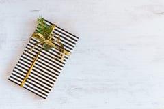 Giftvakje in zwart-wit gestreept document met gouden lint en spartak op een witte houten achtergrond wordt verpakt die Kerstmis c royalty-vrije stock foto's