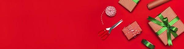 Giftvakjes, verpakkingsdocument, schaar, lint op rode achtergrond Het feestelijk achtergrond, gelukwens, gift verpakken, Kerstmis royalty-vrije stock afbeeldingen