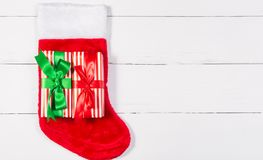 Giftwrapped Presents lying on Christmas Stocking on White Wooden Table Royalty Free Stock Image