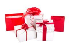 Giftzakken en dozen met rood lint op witte achtergrond Royalty-vrije Stock Fotografie