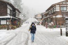 Female tourist holding transparent umbrella and walking on the street with background of Shirakawa-go village stock photos