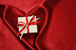 Gify box on red satin Royalty Free Stock Photo