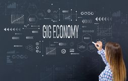 Gig economy with young woman. Writing on a blackboard royalty free stock photo