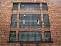 Old factory building big window on the solid red brick facade. Gigant old factory loft building window, made of glass blocks, on the solid red brick industrial Royalty Free Stock Photography
