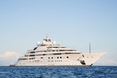 Gigantic big and large luxury mega or super motor yacht on the o. Gigantic big and large luxury mega or super motor yacht on the blue ocean royalty free stock photography