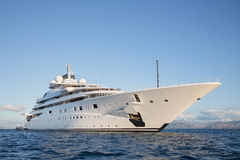 Gigantic big and large luxury mega or super motor yacht on the o. Gigantic big and large luxury mega or super motor yacht on the blue ocean royalty free stock image