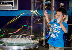Gigantic bubbles and little boy. A little boy plays with gigantic soap bubbles at the colorado children's museum, where science is hands on and learning is fun royalty free stock images