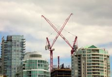 Gigantic cranes being used to construct condos in vancouver. Waterfront apartments being built near the pacific ocean as seen in british columbia in the Royalty Free Stock Photo