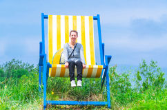 Gigantic Deckchair. With young woman in front of a blue sky stock photos