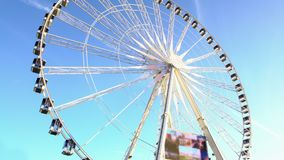 Gigantic observation wheel rotating against cloudless blue sky, entertainment