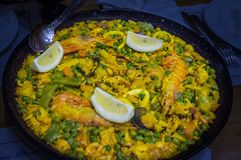 Gigantic paella dish with shrimps and lemon slices Stock Photography