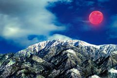 Gigantic super red moon winter landscape highlighting the snow caped mountains of winter. A beautiful winter scene snow caped mountains, a large blood red full royalty free stock photo