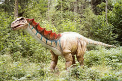 Gigantic statue of realistic dinosaur. In a forest royalty free stock image