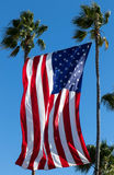 Gigantic United States Flag Hangs Between Palms. A property in Huntington Beach CA USA is displaying a beautiful huge USA flag between two tall palm trees. This Royalty Free Stock Photos