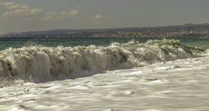 Gigantisk turkos och djupt - grön dyning som kraschar in i stranden på en sommardag för blå himmel i Sicilien arkivbilder