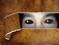 Gigantiskt öga i hål i papperet fotografering för bildbyråer