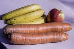 Gigantyczne Organicznie marchewki vs Organicznie banan i duży Organicznie jabłko w Ameryka - tylko Zdjęcie Royalty Free