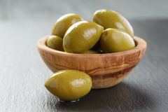 Gigantyczne zielone oliwki w oliwnym pucharze na łupku obrazy stock