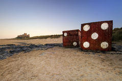 Gigantyczni kostka do gry, Bamburgh kasztel, Northumberland wybrzeże, Anglia. Zmierzch. Obraz Royalty Free