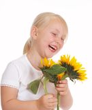 Giggle. Little blond girl giggling with sunflowers in her hands Stock Images