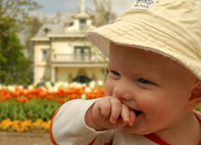 Giggling Baby. Smiling baby in front of a villa with beatytiful tulip garden Royalty Free Stock Image