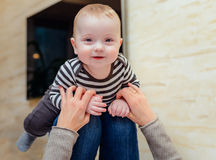 Giggling baby up on knees of adult. Giggling baby in striped shirt up on knees of adult who is holding her hands to simulate flying Royalty Free Stock Photography