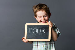 Giggling boy with slate against French 'poux' or head lice. Giggling preschool boy with red hair advertising on a school slate about 'poux' written in French to Stock Photography