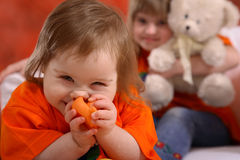 Giggling Handicapped Girl. A cute little girl not quite two years old with Downs Syndrome, holding a toy to her face and giggling Stock Image