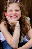 Giggling preteen girl. Giggling little preteen girl with long blond hair, shallow depth of field Royalty Free Stock Images