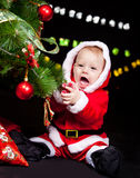 Giggling Santa baby. Sitting beside Christmas tree Royalty Free Stock Images