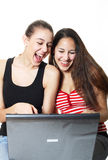 Giggling Teenagers Surf. Two girls laughing and surfing the internet together Stock Photos