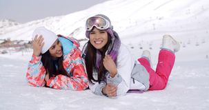 Giggling twins laying down at ski slope stock video