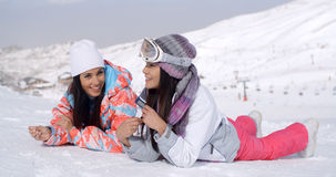 Giggling twins laying down at ski slope Royalty Free Stock Photos