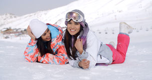 Giggling twins laying down at ski slope Stock Photography