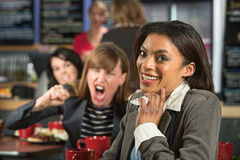 Giggling Woman. Angry lady behind giggling women in coffee house Royalty Free Stock Photos