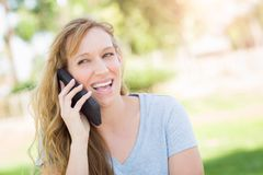 Giggling Young Adult Woman Outdoors Talking on Her Smart Phone. Royalty Free Stock Photography
