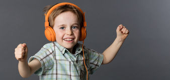 Giggling young boy dancing with winning arms listening to music. Giggling young 6-year old red hair boy with freckles enjoying dancing with winning arms Royalty Free Stock Images