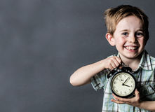 Giggling young child showing retro alarm clock for time concept royalty free stock photo