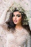 Gigli commoventi della donna attraente caucasica su lei capa su bianco Fotografie Stock