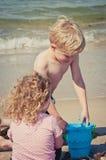 Giirl håller ögonen på hennes broder undersökning och att spela i sanden med en blå hink Royaltyfria Foton