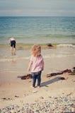 Giirl håller ögonen på hennes broder undersökning och att spela i sanden med en blå hink Royaltyfria Bilder