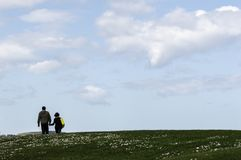 Gijon,阿斯图里亚斯,西班牙,2019年4月09日,走沿愉快谈话的资深夫妇在有天空蔚蓝的公园 免版税图库摄影