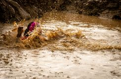 Gijon, Asturias, Spain - February 04, 2019: A female runner splash after jumping into the pit at the mud racer stock images