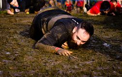 Gijon, Asturias, Spain - February 04, 2019. Trail running athlete crossing the dirty puddle in a mud racer royalty free stock photo